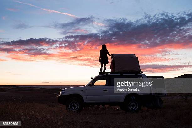 Woman looks out from top of vehicle with tent