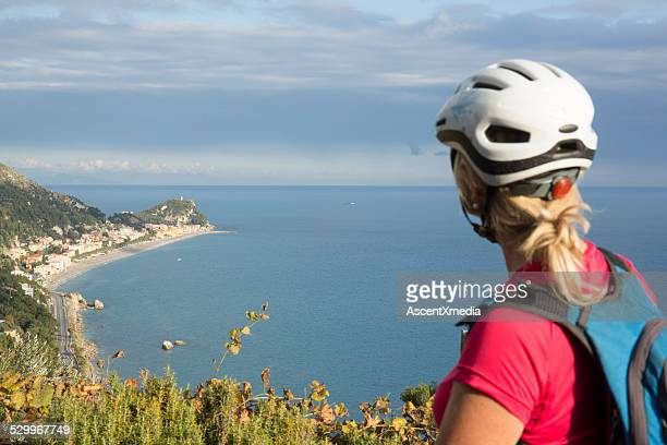 Woman looks out from treed knoll al mar