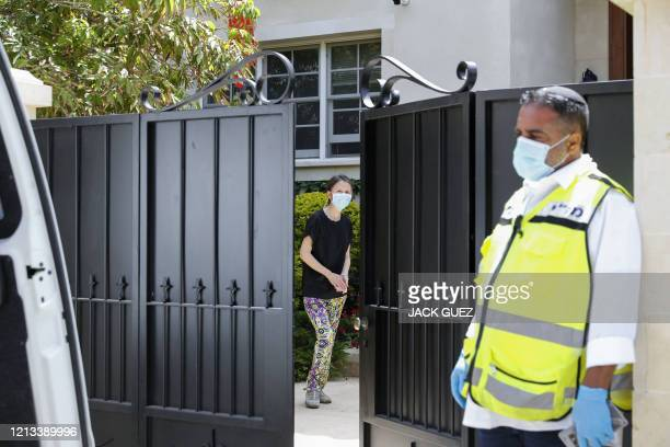 Woman looks out from within the gated house of the Chinese ambassador in Israel where he was found dead, and which was cordoned-off by the police, in...
