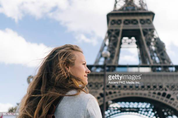 Woman looks out in front of the Eiffel Tower