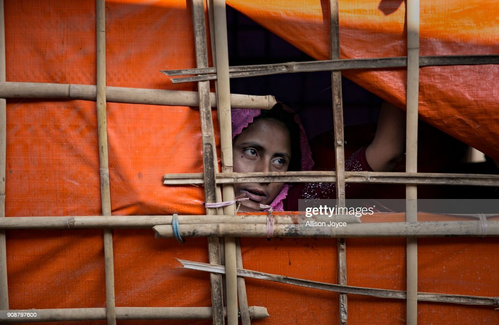 COX'S BAZAR, BANGLADESH - JANUARY 17: A woman looks out of her tent on January 17, 2018 in Cox's Bazar, Bangladesh. In the refugee settlement of Balukhali, over 116 widows and orphans have found shelter within a dense settlement of 50 red tents where no men or boys over the age of 10 years old are allowed. More than 655,000 Muslim Rohingya have crossed the border into Bangladesh since August last year, when they fled Rakhine state after the Myanmar military launched a brutal crackdown which was described by the United Nations as 'ethnic cleansing'. Women and girls reportedly make about 51 percent of the distressed and traumatized Rohingya population in the refugee camps and face a high risk of being victims of human trafficking and sexual abuse, while adolescent girls aged between 13 and 20 risk getting involved in forced marriages. Many of the Rohingya women travelled alone after their husbands had been killed or taken away during the attacks on Rohingya villages as many continue to fear returning home due to the lack of security guarantees.