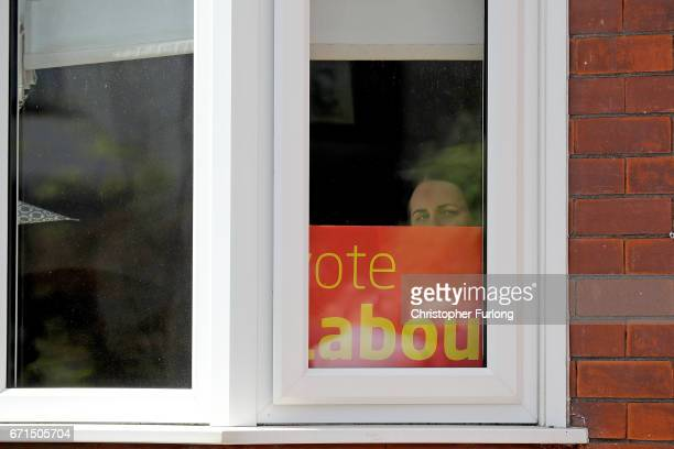 A woman looks out of her window as Labour party leader Jeremy Corbyn talks to party members and activists on the streets of Warrington on April 22...