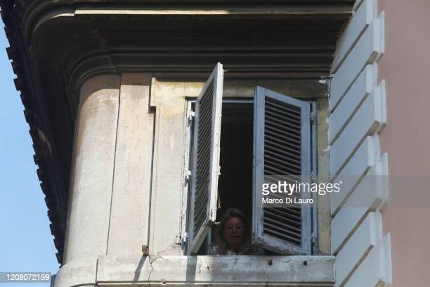 A woman looks out of the blinds of her home on March 22 2020 in Rome Italy As Italy extends its nationwide lockdown to control the spread of COVID19...