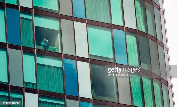 Woman looks out of the window in an inner-city hotel where travellers returned from overseas are staying in isolation in Melbourne on March 30, 2020....
