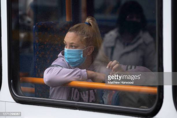 Woman looks out of the window of a bus while wearing a surgical face mask on September 8, 2020 in Caerphilly, Wales. The county borough of Caerphilly...