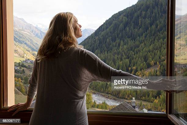 Woman looks out of window to mountains