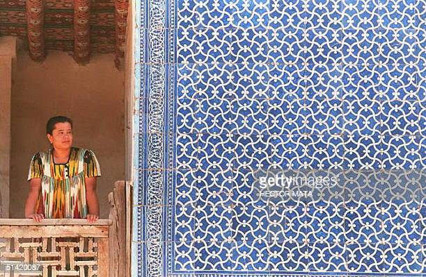 A woman looks out onto the street from the balcony of the AllaKuli Palace next to a mosaiccovered wall in the old town of Khiva Uzbekistan on the old...