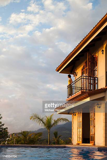 A woman looks out over a pool from a balcony at a hotel as the sun sets.