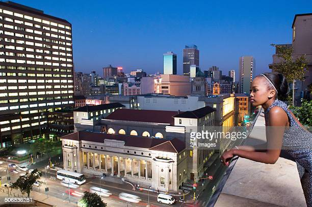 A woman looks out over balcony of city apartment at night in Johannesburg, South Africa.