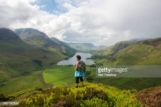 a woman looks out over buttermere from fleetwith pike, lake district national park, cumbria, england, united kingdom, europe - alex pike stock pictures, royalty-free photos & images