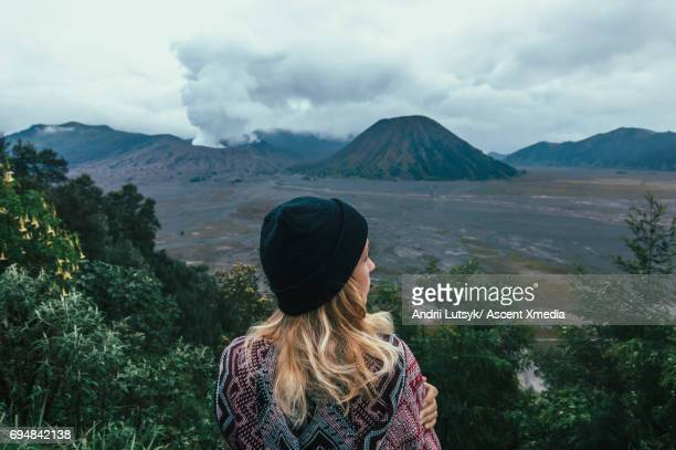 Woman looks out over volcanic plain, from above