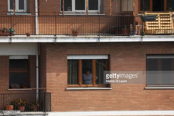 A woman looks out the window during lockdown on March 23 2020 in Rome Italy As Italy extends its nationwide lockdown to control the spread of COVID19...