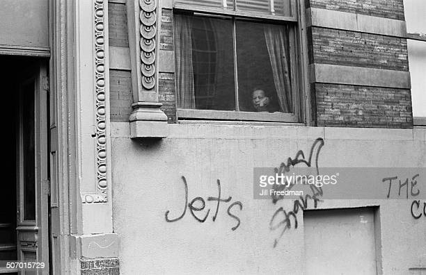 A woman looks out the window from a tenement building on the Lower East Side New York City USA 1966