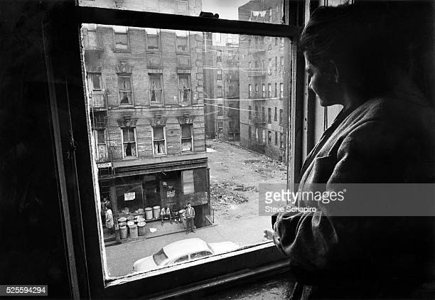 Woman looks out the window of an East Harlem apartment