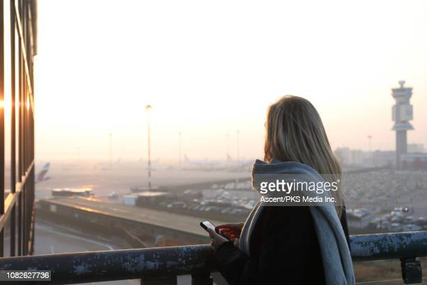 Woman looks out to airport tarmac and sunrise