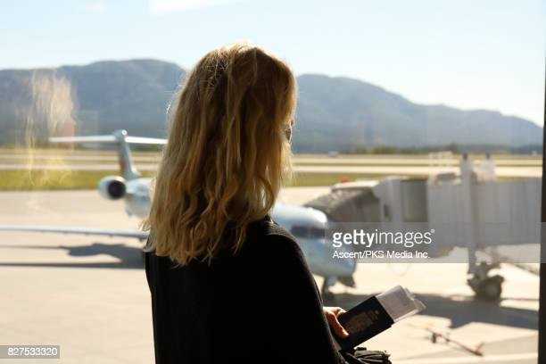 Woman looks out to jet on tarmac, at airport
