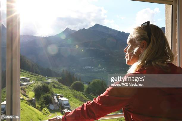 Woman looks out to mountain ranges from window