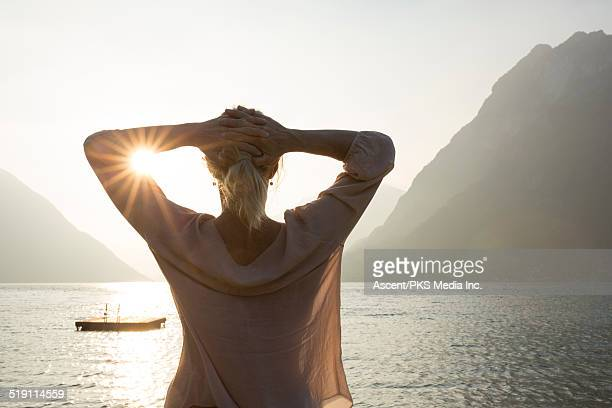 Woman looks out to raft and tranquil mtn lake