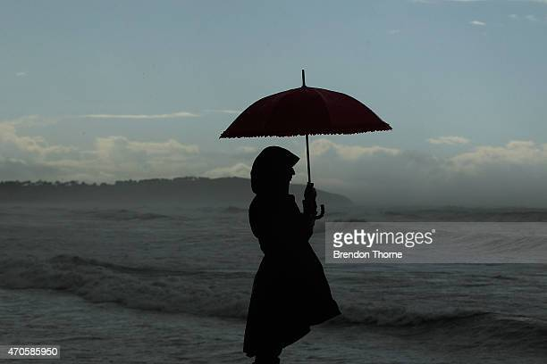 A woman looks out to sea at Dee Why beach on April 22 2015 in Sydney Australia Three people have died and more than 200000 are still without power as...