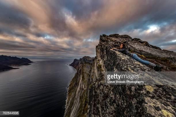 Woman looks out to sea from Segla Peak on Senja Island in autumn, Arctic Norway