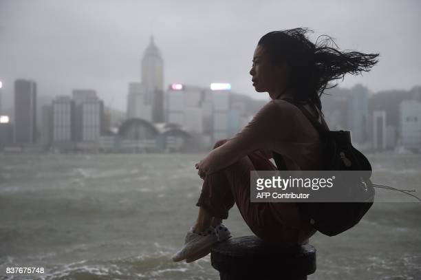 A woman looks out to Victoria Harbour during heavy winds and rain brought on by Typhoon Hato in Hong Kong on August 23 2017 Typhoon Hato smashed into...