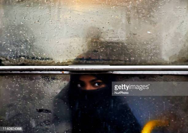 A woman looks outside from a bus window in Kolkata on 03 May 2019 as the cyclonic storm Fani hits the coastal places of Orissa and West Bengal on 03...