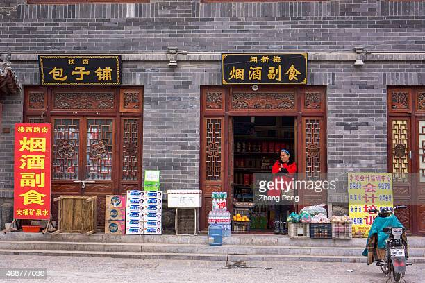 A woman looks outside from her grocery store After rapid growth and development China is facing great challenge of the rising income inequality