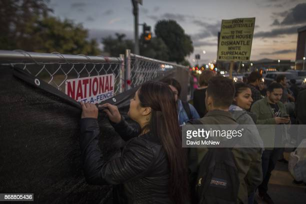 A woman looks over a fence erected to keep protesters away from the site of a speaking appearance by Conservative provocateur Milo Yiannopoulos...