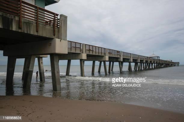 Woman looks over calm seas at Juno Beach Pier in Juno Beach, Florida on September 4, 2019. - Hurricane Dorian churned towards the United States...
