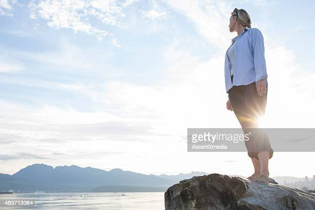 Woman looks over her shoulder towards mountains