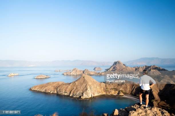 mujer mira sobre islas dispersas en el mar de flores - flores indonesia fotografías e imágenes de stock