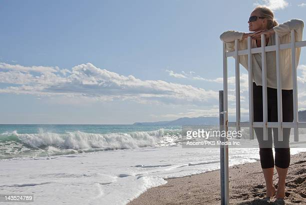 Woman looks over white fence, to crashing surf
