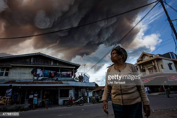 A woman looks skyward as Mount Sinabung spews pyroclastic smoke seen from Simpang Empat village on June 19 2015 in Karo District North Sumatra...