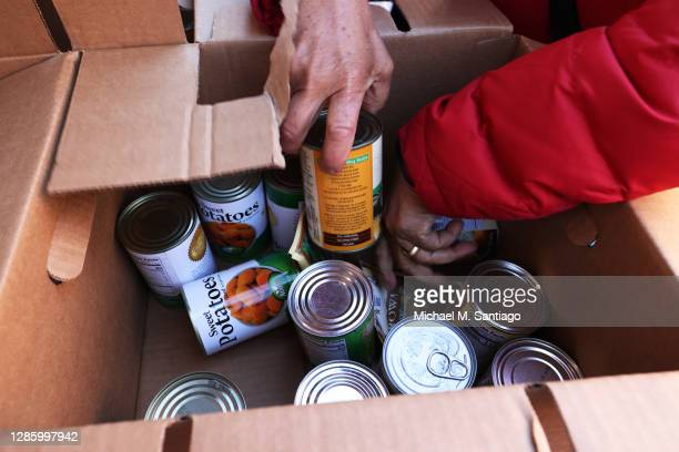Woman looks through a box of canned food during a Thanksgiving food distribution event at Food Bank For New York City in the Harlem neighborhood on...