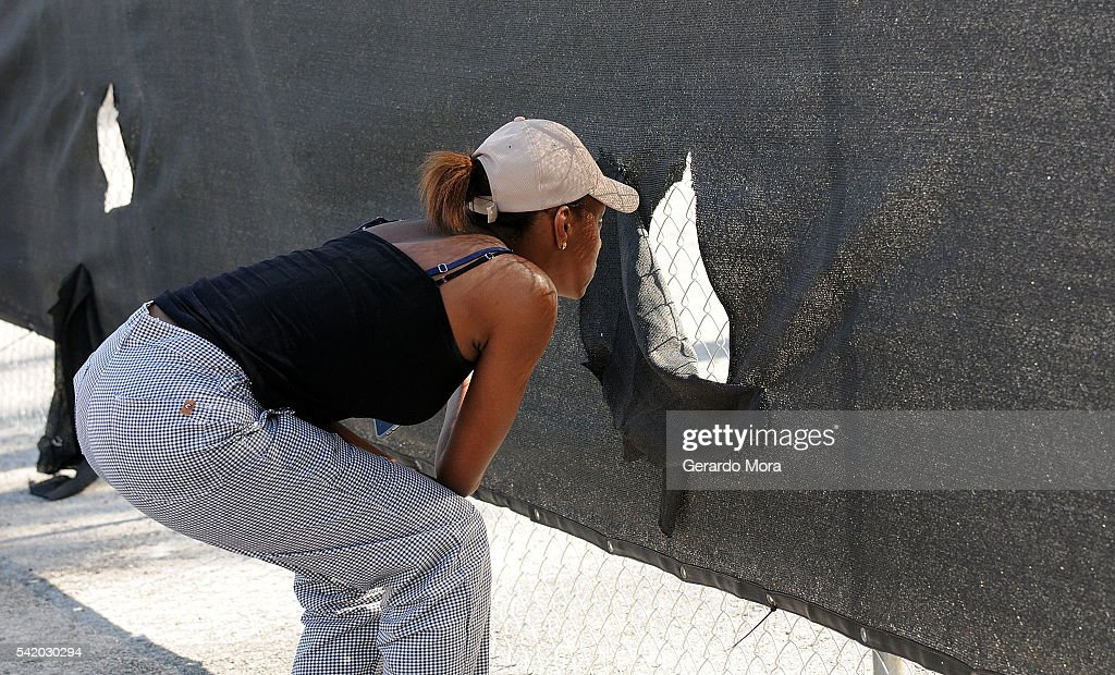 A woman looks through a fence at the site of the Pulse Nightclub building on June 21, 2016 in Orlando, Florida. The Orlando community continues to mourn the victims of the deadly mass shooting at a gay nightclub.