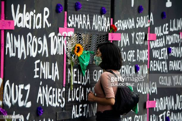 Woman looks through a metal fence surrounding the National Palace ahead of the International Women's Day, in Mexico City on March 7, 2021.