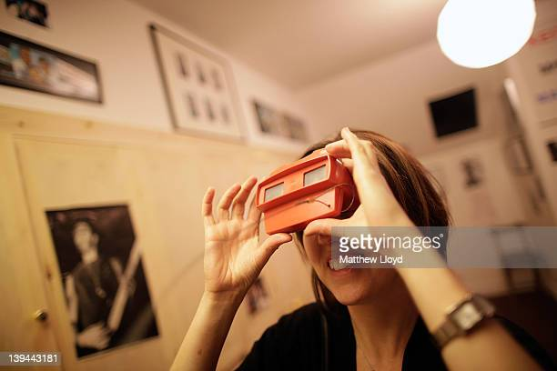 A woman looks through a photo viewer at the 'Open Bedroom' installation part of Jeremy Deller's exhibition at the Hayward Gallery on February 21 2012...