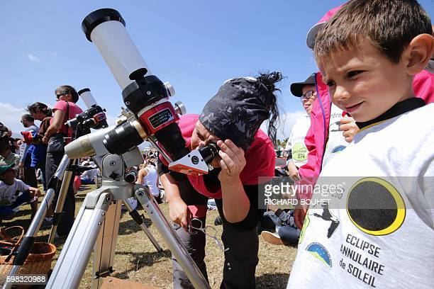Woman looks through a telescope an annular solar eclipse, on September 1 in Saint-Louis, on the Indian Ocean island of La Reunion. Stargazers in...