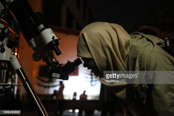A woman looks through a telescope at the longest lunar eclipse of the 21st Century in Jakarta Indonesia on Saturday July 28 2018 The longest...