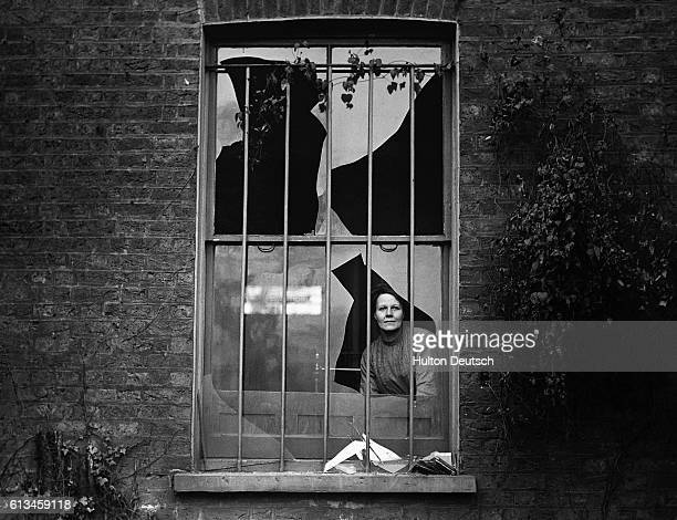 A woman looks through a window in a house near Holloway prison broken by the blast after the suffragettes tried to blow the prison up | Location...