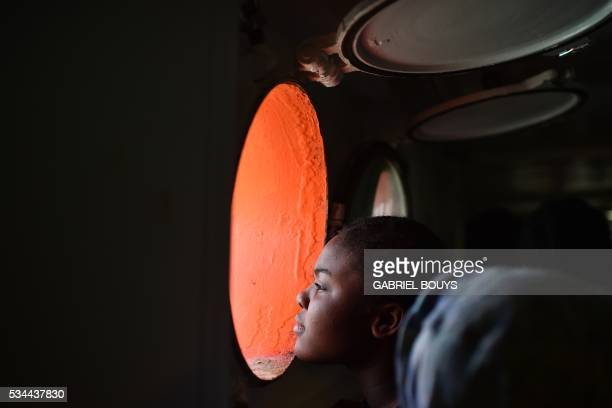 TOPSHOT A woman looks through a window of rescue ship 'Aquarius' as more the 380 migrants arrive in the port of Cagliari Sardinia on May 26 two days...