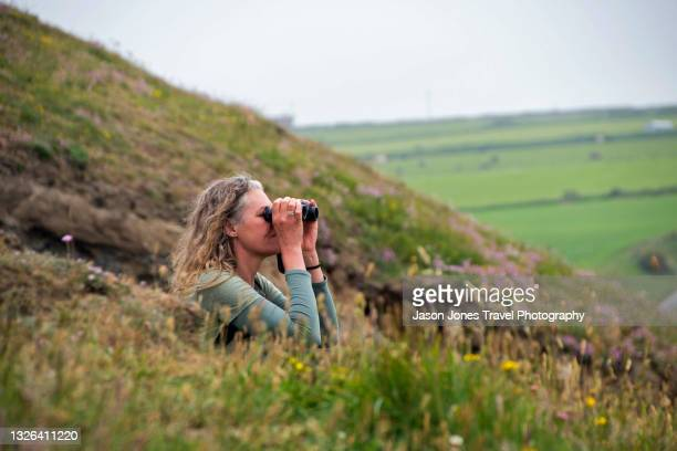 a woman looks through binoculars at the coast - newport wales stock pictures, royalty-free photos & images