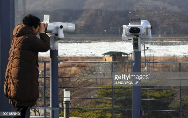 A woman looks through binoculars during a visit to the Imjingak peace park near the Demilitarized Zone dividing the two Koreas in the border city of...