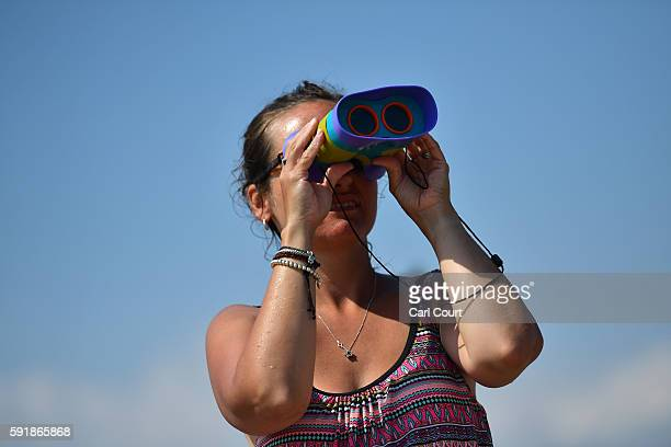 A woman looks through binoculars during the Bournemouth Air Festival on August 18 2016 in Bournemouth England The air show runs from the 18th to 21st...