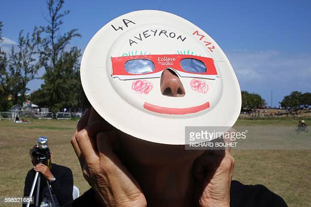 A woman looks through eclipse viewing glasses an annular solar eclipse on September 1 in SaintLouis on the Indian Ocean island of La Reunion...