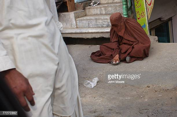 A woman looks through her burqua to check the contents of her begging bowl October 11 2007 in Mingora in the Swat Valley of Pakistan Once one of the...