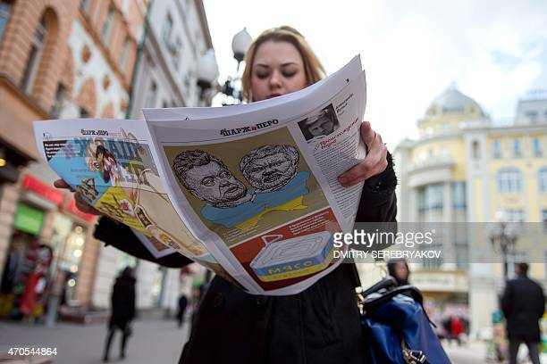 A woman looks through her copy of the first issue of satirical weekly magazine Sharzh i Pero as she walks along a street in central Moscow on April...
