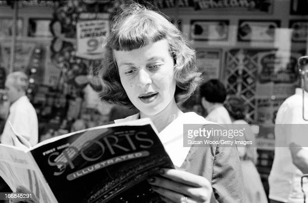 A woman looks through the premiere issue of Sports Illustrated magazine on a Manhattan sidewalk New York New York August 16 1954