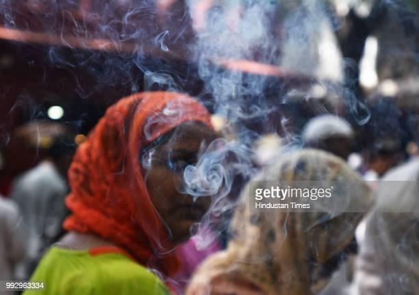 A woman looks through the smoke of the incense sticks at the shrine of Sufi saint Hazrat Syed Muhammad Nizamuddin Auliya at the Nizamuddin Dargah on...