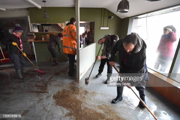 A woman looks through the window as people sweep mud from Barbary's Cafe following severe flooding beside the River Calder on February 10 2020 in...